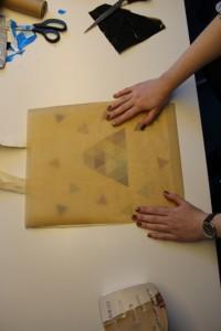 Lege vorsichtig einen Bogen Backpapier auf den Stoff mit den ausgeschnittenen Motiven und schalte das Bügeleisen auf eine mittlere Stufe.