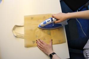 Platziere das Bügeleisen über dem Motiv, das du aufbügeln möchtest. Lege es die ersten zehn Sekunden einfach auf, dann bewege es gleichmäßig hin und her. Bügele ungefähr eine Minute lang, überprüfe aber vorsichtshalber nach 30 Sekunden, ob das Motiv schon am Stoff haftet.